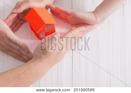 hands and paper house on white wooden background