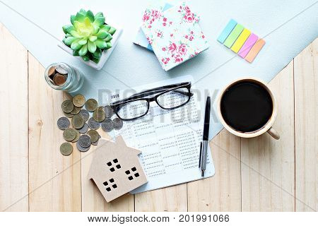 Business, finance, saving money, banking, property loan or mortgage concept :  Top view or flat lay of wood house model, saving account book or financial statement and coins on office desk table