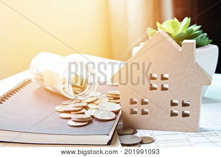 Business, finance, saving money, banking, property loan or mortgage concept :  Wood house model and coins scattered from glass jar on office desk table