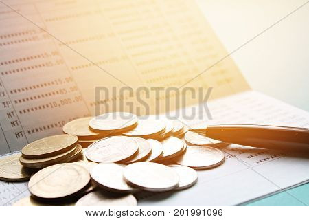 Business, finance, savings or loan concept : Pen and coins on saving account passbook or financial statement