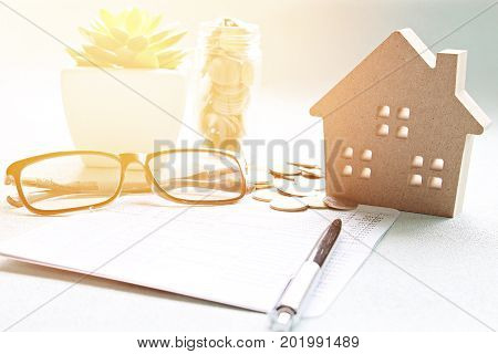 Business, finance, saving money, property ladder or mortgage loan concept :  Wood house model, saving account book or financial statement and coins on office desk table