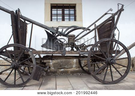 An old carriage that binds to a horse. An old carriage that binds to a horse. The plow and blade are loaded on the carriage.