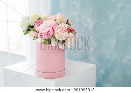Flowers in round luxury present box. Bouquet of pink and white peonies in paper box near the window.Mock-up of hat box of flowers with free copyspace for text. Interior decoration in in pastel colors