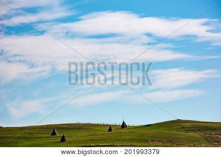 Hay Stacks On Hillside Under The Beautiful Sky