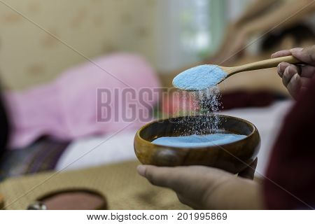 Spa concept. Bowl with blue sea salt close up candles and sea salt Spa Thai setting for aroma therapy and sugar and salt massage with flower on the bed relax and healthy care Healthy Concept