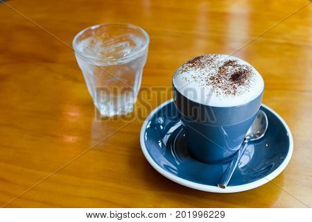 Capuccino Coffee on glass on wood table