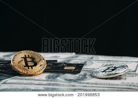 Golden bitcoin with credit card on top of dollar banknote background new currency accepting bitcoin for payment finance concept copy space