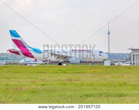 Stuttgart Germany - April 29 2017: Airbus airplane A320 from Eurowings at ground (airport Stuttgart) TV Tower (Fernsehturm) in background - green meadow in front