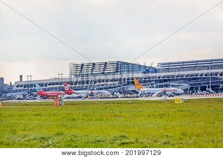 Stuttgart Germany - May 06 2017: Airport Stuttgart Terminal with airplanes in parking position exterior view with runway and green meadow in front