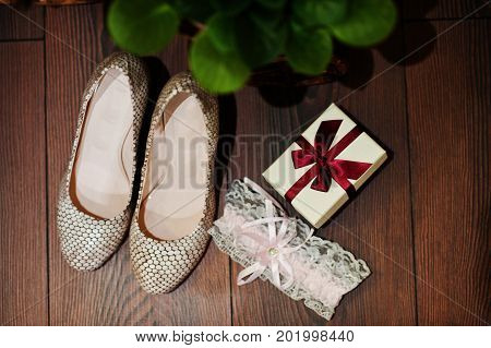 Close-up Photo Of Wedding Shoes, Garter And Tiny Box With Red Ribbon.
