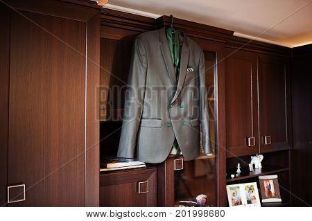 Groom's Wedding Tuxedo Hanging On The Rack On The Wardrobe.