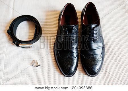 Close-up Photo Of Groom's Black Shoes, Belt And Golden Cufflinks.