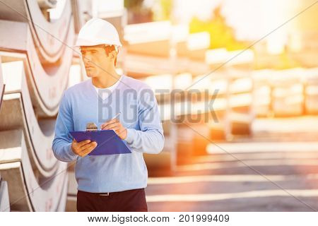 Male supervisor with clipboard inspecting stock at site