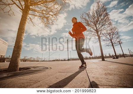 Never give up and keep moving! Full length of beautiful young woman in sports clothing running in city streets at the morning sunrise time.Aspiration move