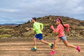 Trail run race ultra runners athletes couple running in rock path in nature landscape. Ultra runner people competing on cross country competition working out endurance on volcanic rocks outdoors poster