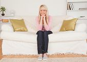 Beautiful blonde woman posing while sitting on a sofa in the living room poster