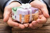 Cropped image of businessman holding gift box made from euro papernotes at wooden table poster