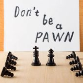 Bowed servants in front of managers chess pieces king queen and pawns symbolizing people of different statuses against the motivating inscription in English do not be a pawn poster