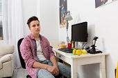 Teenage boy sitting on chair at computer table in his room. Boy with demotivative face in his room sitting in front of computer. poster
