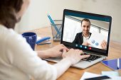 Businesswoman talking on video conference to businessman showing document at webcam, colleagues discussing work by video call application, financial consultant consulting client online, close up view poster