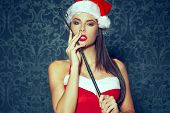 Sexy santa dominatrix woman posing with whip on vintage background poster