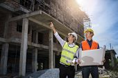Businessman engineer looking blueprint in a building to discussion with architects at construction site or building site of highrise building poster