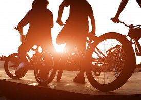 Cyclists on the ramp for jumping at sunset