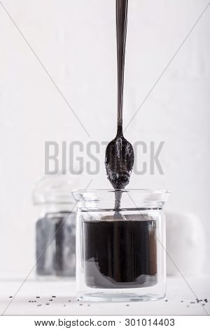 Black Tahini Sauce In Glass Jar On White Background. Natural Paste Made From Black Sesame Seeds.
