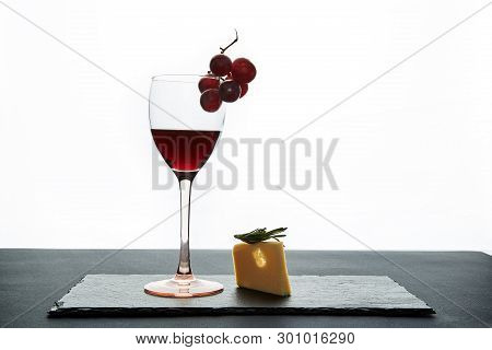 Glass Of Red Wine Garnished With Grape And Piece Of Savory Hard Cheese On Slate Dish