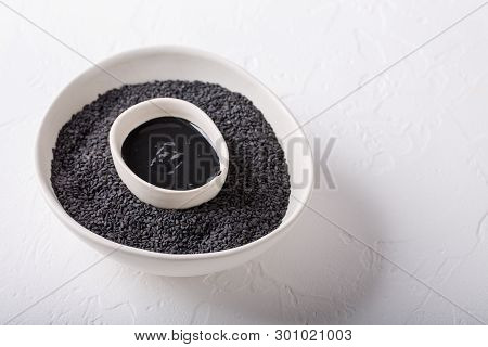 Black Tahini Sauce And Black Sesame Seeds In Bowls On White Background. Natural Paste Made From Sesa
