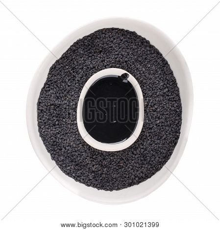 Black Tahini Sauce And Black Sesame Seeds In White Bowls Isolated On White Background. Natural Paste