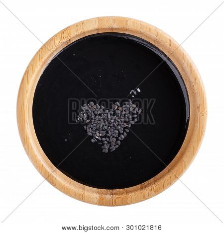 Black Tahini Sauce In Wooden Bowl Isolated On White Background. Natural Paste Made From Sesame Seeds