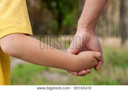 Mutter hält eine Hand seines Sohnes im Frühling im freien