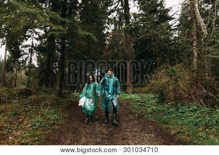 Together Overcome Any Difficulties. Bride And Groom Dressed In Raincoats Go Through The Swamp On The