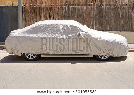 A Car Parked With Protective Cover Silver. Car Under A Protective Cover Parked In The Courtyard In S
