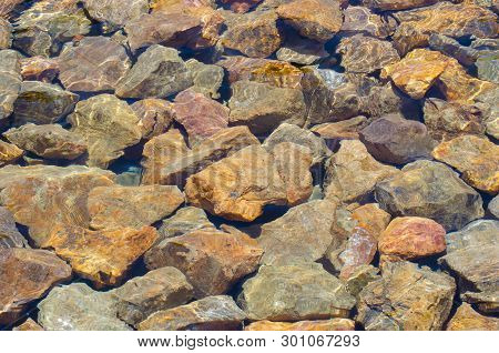 Colorful Rocks Covered By Clear, Still Water With A Few Ripples.  Background.  Sunny Water Ripples O