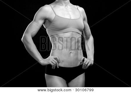 Black and white portrait of a female fitness bodybuilder posing against black background
