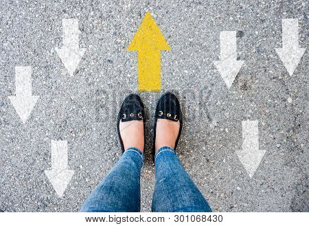 Woman Shoes On Asphalt And Opposing Direction Arrows On Asphalt Ground, Personal Perspective Footsie