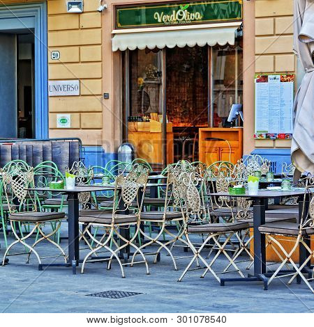 Yellow Facade Of A Building Of Alfresco Tuscany Tavern Verd Oliva With A Patio, Small Tables, Chairs