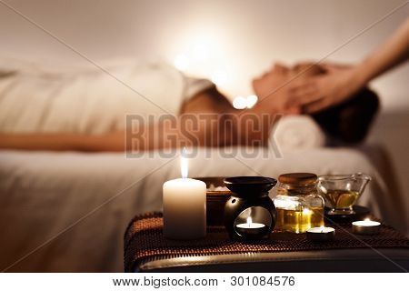 Aroma Spa. Girl Enjoying Massage In Luxury Spa With Candles On Foreground