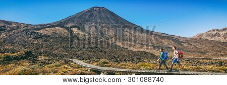New Zealand Hiking Couple Backpackers Tramping At Tongariro National Park. Two hikers hiking by Mount Ngauruhoe. People living healthy active lifestyle outdoor panoramic banner.