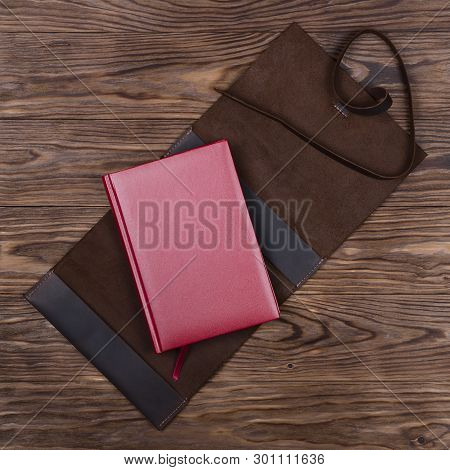 Brown Opened Handmade Leather Notebook Cover With Red Notebook Inside On Wooden Background. Stock Ph
