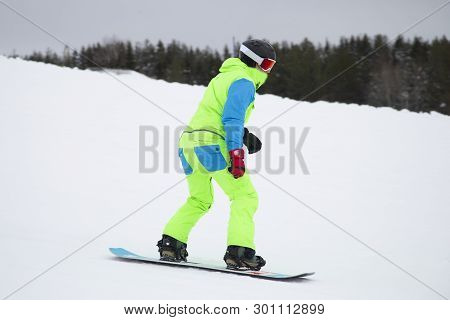 Snowboarder On A Snowboard . Snowboarder Jumping From The Mountain On A Snowboard In Winter.