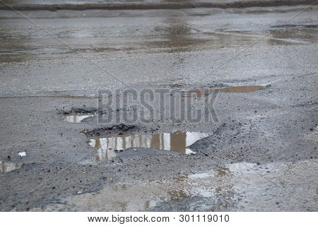 Water Filled Potholes On A Rough Road.several Potholes. Bits Of Gravel On Road. Puddles (potholes) O