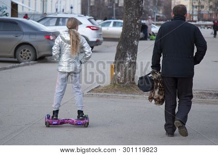 Syktyvkar,komi/ Russia, April 14,2019/children Repent On A Scooter On A City Street.
