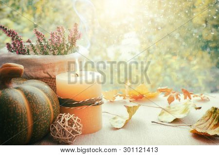 Burning Candle, Hokkaido Pumpkin And Fall Decorations On A Windowboard On A Rainy Day, Space For You