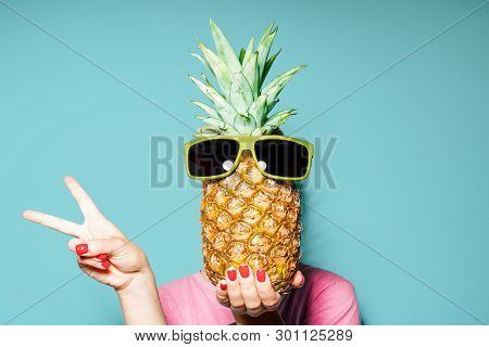Woman And Pineapple On Her Head Standing Over Color Background