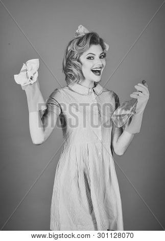 Housekeeper in uniform with clean spray, duster. Pinup woman hold soup bottle, duster. Cleanup, cleaning services, wife, gender. Retro woman cleaner on blue background. Cleaning, retro style, purity. poster