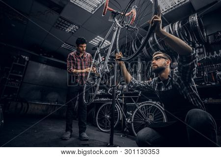 Two Attractive Mans Are Working On Bicycle Fixing In Dark Workshop.