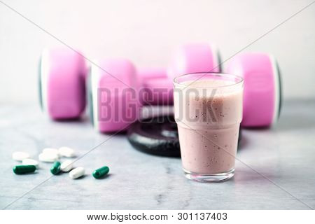 Glass Of Protein Shake With Milk And Raspberries. Bcaa Amino Acids, L - Carnitine Capsules And Pink